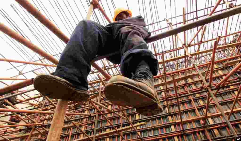 在肯尼亚首都内罗毕附近,一名建筑工人在内罗毕-锡卡公路的一座新桥上搭建脚手架(2010年9月13日)。这条公路由中国的武夷、中水电和胜利工程公司承建,肯尼亚和中国政府以及非洲开发银行出资。据中国公司说,项目耗资280亿肯尼亚先令(3亿3千万美元)。