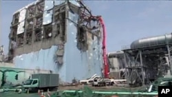 A concrete pumping vehicle sprays water to the spent fuel pool of No.4 reactor at Tokyo Electric Power Company's Fukushima Daiichi Nuclear Power Station in Fukushima prefecture in this handout photo taken May 6, 2011 and released by TEPCO on May 17, 2011