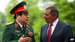 U.S. Defense Secretary Leon Panetta, right, speaks with Vietnamese Defense Minister Phung Quang Thanh during an arrival ceremony at the Ministry of Defense in Hanoi, Vietnam Monday, June 4, 2012. (AP Photo/Jim Watson, Pool)