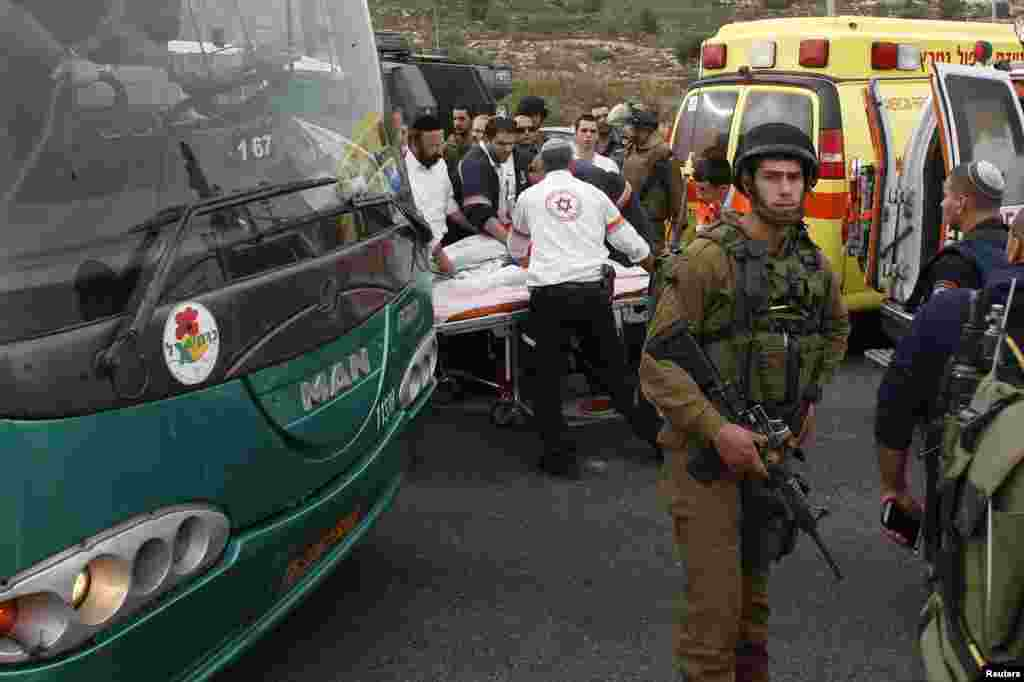 An Israeli soldier stands guard as medics evacuate an injured girl from the scene where a Palestinian attacked civilians with a chemical substance near the settlement of Neve Daniel, Dec. 12, 2014.