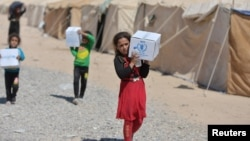 Displaced children from Syria receive aid supplies at a refugee camp in Baiji, north of Baghdad, Sept. 9, 2016.
