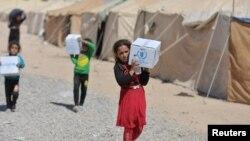 2016年9月9日巴格达一个难民营里来自叙利亚的难民接受援助物资。