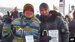 参加2月4日莫斯科反政府示威的亚里山大(左)和安东(右)。两人手中的传单:普京还要干12年?谢谢,不要。