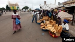 Street vendors sell loaves of bread and other wares on a street in Bouake, Ivory Coast, December 2010.