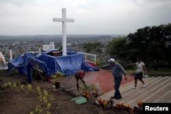 Para pekerja membersihkan Loma de la Cruz, sehari sebelum kunjungan Paus Fransiskus ke Holguin di Kuba, 20 September 2015.