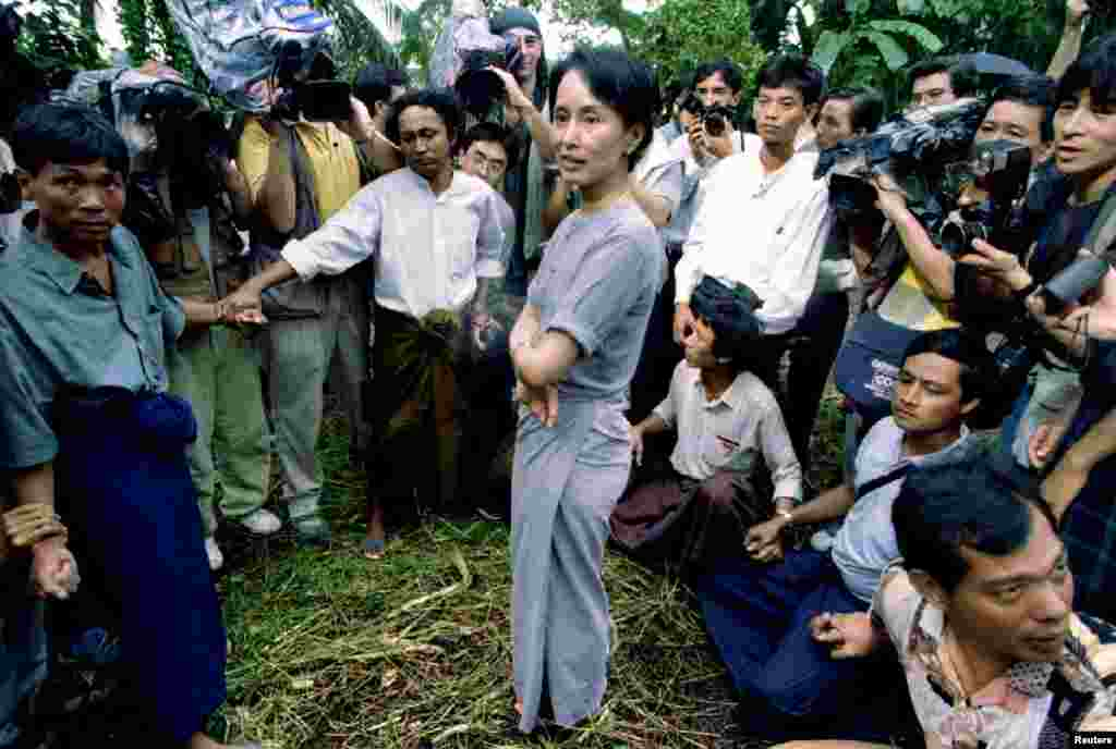 Aung San Suu Kyi is surrounded by security guards and newsmen as she walks out of her lakeside house in Rangoon, Burma, Juy 14, 1995.