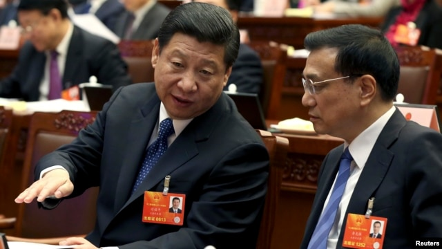 China's Communist Party Chief Xi Jinping speaks to Vice Premier Li Keqiang, presidium of the first session of the 12th National People's Congress, Beijing, March 4, 2013.