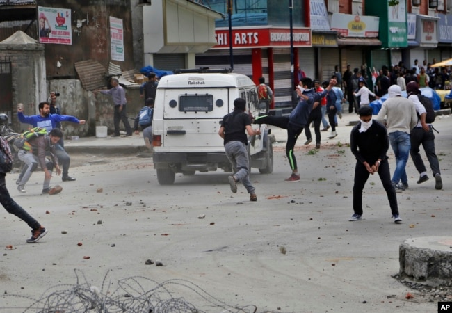 Kashmiri students and other protesters throw stones at an Indian police vehicle as they clash with police in Srinagar, Indian controlled Kashmir, April 24, 2017.