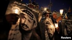 Palestinci nose sveće i poster sa likom Jasera Arafata