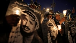 Palestinians hold candles and posters depicting late Palestinian leader Yasser Arafat during a rally marking the 9th anniversary of his death in Jerusalem's Old City on November 11, 2013.