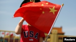 一名站在北京天安门广场的小男孩身穿美国T恤手拿中国国旗。(2019年5月7日)