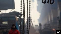 河北省唐山曹妃甸港的一名碼頭工人等待把鋼筋裝上貨輪。 (2012年2月20日)