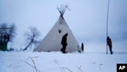 Snow lays on the ground as campers from Colorado set up a teepee at the Oceti Sakowin camp where people have gathered to protest the Dakota Access oil pipeline near Cannon Ball, N.D., Nov. 30, 2016.