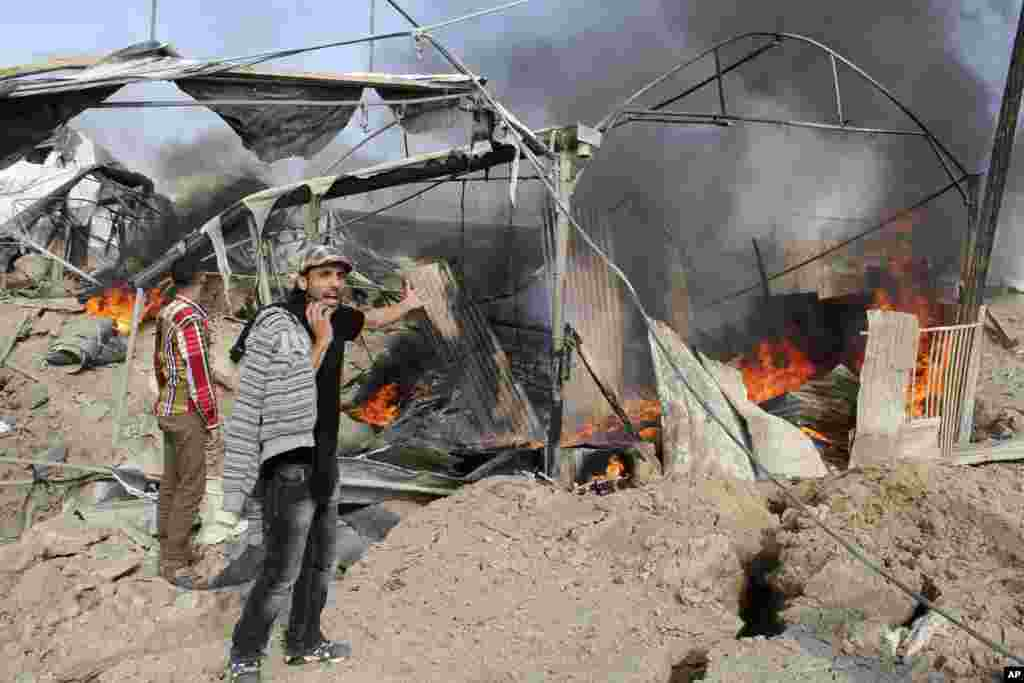 A Palestinian man reacts as flames and smoke rise from a smuggling tunnel after an Israeli strike along the border between Egypt and Rafah in the southern Gaza Strip, November 21, 2012.