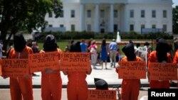 Các nhà hoạt động nhân quyền trong bộ quần áo tù nhân màu cam và khăn bịt đầu, đại diện cho các tù nhân ở nhà tù Guantanamo, Cuba, đứng trước Tòa Bạch Ốc phản đối việc Tổng thống Obama vẫn chưa đóng cửa nhà tù này. (AP Photo/Pablo Martinez Monsivais)