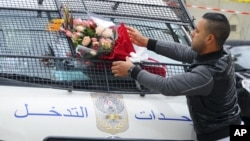 A man places a bouquet of flowers on a police van, near the bus that exploded in Tunis, Nov.25, 2015.