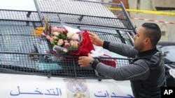 Un homme place un bouquet de fleurs devant une fourgonnette de la police près du lieu de l'attaque contre un bus de la garde de la sécurité présidentielle à Tunis, 25 novembre 2015.