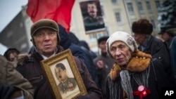 FILE - A man holds a portrait of Soviet dictator Josef Stalin during a demonstration marking the 99th anniversary of the 1917 Bolshevik Revolution in Moscow, Russia, Nov. 7, 2016.