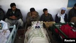 کوئٹہ کی ایک امام بارگاہ میں رکھی میتوں کے پاس لواحقین افسردہ بیٹھے ہیں۔