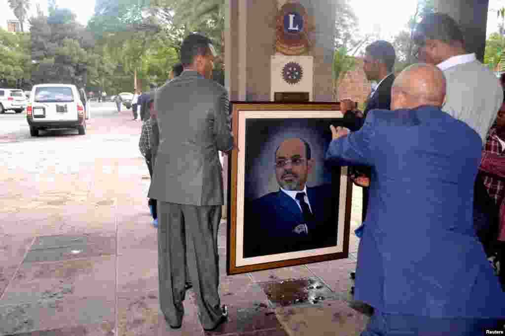 Officials move a portrait of Meles shortly after the announcement of his death in Addis Ababa, August 21, 2012.