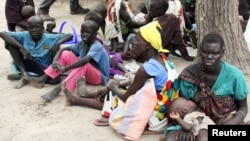 FILE - Residents displaced by fighting between government and rebel forces are seen at a World Food Program (WFP) outpost in Kuernyang Payam, South Sudan, May 2, 2015.