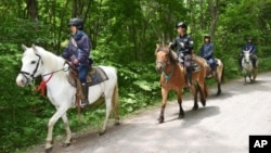 Rescuers on horseback search for a 7-year-old boy who is missing in a Japanese forest in northern Japan. He has been missing since late Saturday afternoon after his parents reportedly made him get out of the car as punishment. (Ichinoshin Matsuhashi/Kyodo News via AP