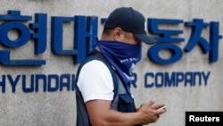 Seorang karyawan Hyundai Motor berdiri di depan logo perusahaan pembuat mobil tersebut di pabrik mereka di Asan, selatan Seoul (Foto: dok). Sekitar 40 ribu karyawan Hyundai Motor Co.kembali mogok kerja, memrotes keputusan perusahaan untuk mengeluarkan dana $10 milyar untuk membeli lahan bagi pendirian kantor baru.