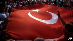 Protesters wave a large Turkish flag during an anti-coup rally in Taksim Square in Istanbul, July 25, 2016.
