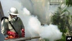 El brote de dengue también lo acreditan los especialistas a la falta de políticas a nivel nacional para controlar el vector que causa la infección. En la foto un empleado fumiga un vecindario en Caracas.
