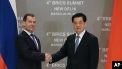 中国国家主席胡锦涛(右)3月28日在新德里与俄罗斯总统梅德韦杰夫握手