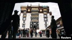 FILE - Pilgrims and tourists visit Potala Palace in Lhasa in Tibet Autonomous Region.
