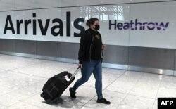 Seorang penumpang mengenakan masker tiba di bandara Heathrow, London barat, Inggris, di tengah pandemi Covid-19,10 Juli 2020