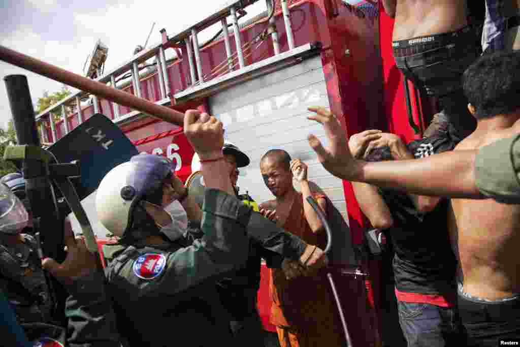 Police use batons against garment workers during clashes in Phnom Penh, Cambodia, Nov. 12, 2013.
