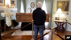 A man pauses by the casket as he pays respects to Billy Graham during a public viewing at the Billy Graham Library in Charlotte, North Carolina, Feb. 26, 2018.