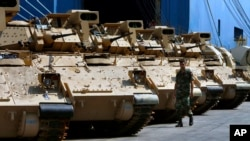 A Lebanese army soldier walks near military vehicles that were unloaded from a ship at Beirut's port in Lebanon, Aug. 14, 2017.