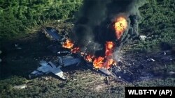 In this frame from video, smoke and flames rise from a military plane that crashed in a farm field, in Itta Bena, Mississipi, July 10, 2017, killing several.