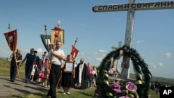 A religious procession passes an Orthodox cross with a sign reading Save and Guard at the crash site of the Malaysia Airlines Flight 17, near the village of Hrabove, eastern Ukraine, July 17, 2015.
