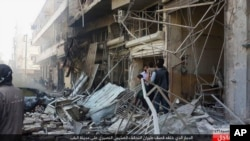 In this Oct. 5, 2015 photo released by the Rased News Network, a Facebook account affiliated with Islamic State militants, which has been authenticated based on its contents and other AP reporting, people gather at the site of an airstrike in Al-Bab on the outskirts of Aleppo, Syria.
