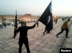 FILE - An Islamic State fighter hoists the terrorist group's flag and a weapon in the Iraqi city of Mosul, June 23, 2014.