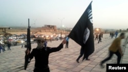 FILE - An Islamic State fighter hoists the terrorist group's flag.