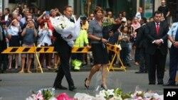 PM Australia Tony Abbott dan istrinya Margie, bersama massa pelayat meletakkan bunga di lokasi peringatan sementara bagi korban penyanderaan di Sydney, Selasa (16/12).
