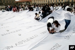 "Demonstrators install white sheets covered with the names of victims of Colombia's internal conflict in downtown Bogota, Colombia, October 11, 2016. The giant quilt is part of artist Doris Salcedo's ""Adding Absences"" project."