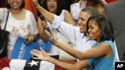 奥巴马总统和夫人5月5日在维吉尼亚州立邦联大学的集会上向人群挥手致意