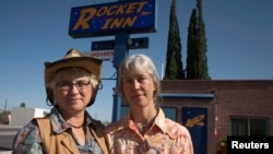 Val Wilkes, 54, (L) and her wife Cydney Wilkes, 56, stand outside their motel, the Rocket Inn, in Truth or Consequences, New Mexico May 2, 2014. (REUTERS/Lucy Nicholson)