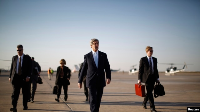 U.S. Secretary of State John Kerry, second from right, walks across the tarmac of Baghdad International Airport as he prepares to board an aircraft out of the Iraqi capital, Mar. 24, 2013.