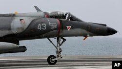 FILE - A French military plane lands on the French navy aircraft carrier Charles de Gaulle in the Persian Gulf.