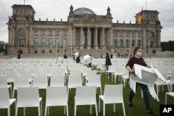 Aktivis menata kursi di 'Platz der Republik' di depan gedung Reichstag, di Berlin, Jerman, sebagai bagian dari hari aksi anti-rasis nasional, Senin, 7 September 2020.