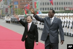 FILE - Taiwan's then-president, Chen Shui-bian, left, and Blaise Compaoré, who was then president of Burkina Faso, wave to well-wishers during an honor guard review, Nov. 20, 2006, in front of the Presidential Office in Taipei, Taiwan. Burkina Faso has now severed those formal ties. Today, fewer than 20 nations recognize Taiwan's independence.