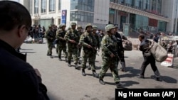 Heavily armed Chinese paramilitary police men march past the site of the late April explosion outside the Urumqi South Railway Station in Urumqi in northwest China's Xinjiang Uygur Autonomous Region. China blames Islamic extremists for this and other recent deadly attacks.