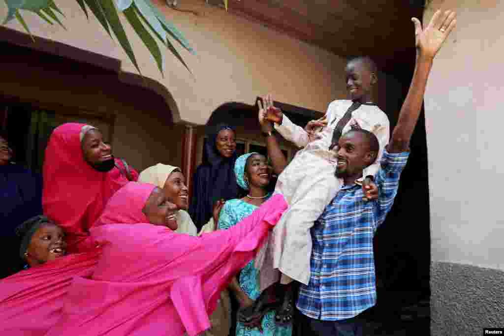 Muhammed Bello, a rescued student, is carried by his father as his relatives celebrate after he retuned home in Kankara, Nigeria, Dec. 19, 2020.